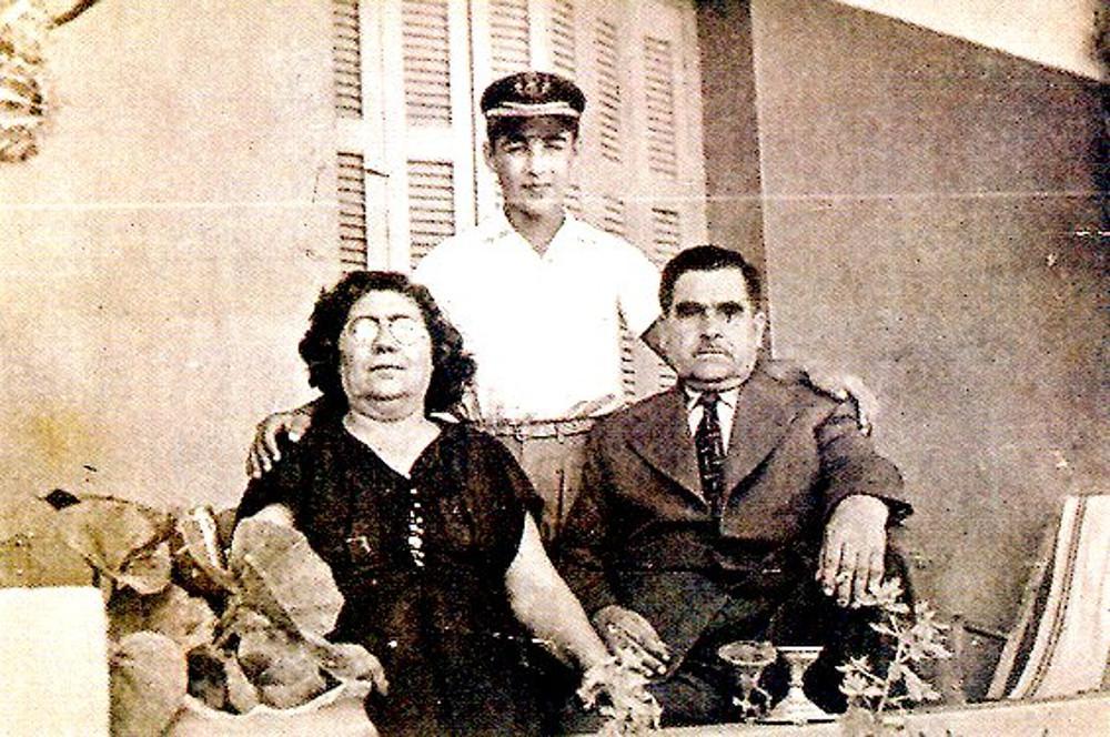 Ο Τόλης Βοσκόπουλος με σχολικό καπέλο και τους γονείς του στο σπίτι τους το 1952.